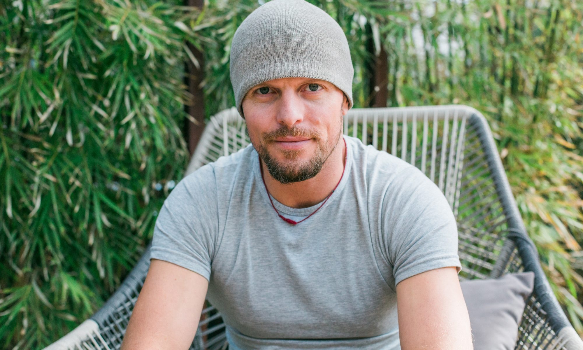 Tim Ferriss sitting in a large patio chair in front of a patch of bamboo.